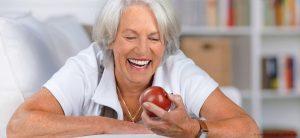 ältere dame schaut einen apfel an und lacht mit schönen zähnen